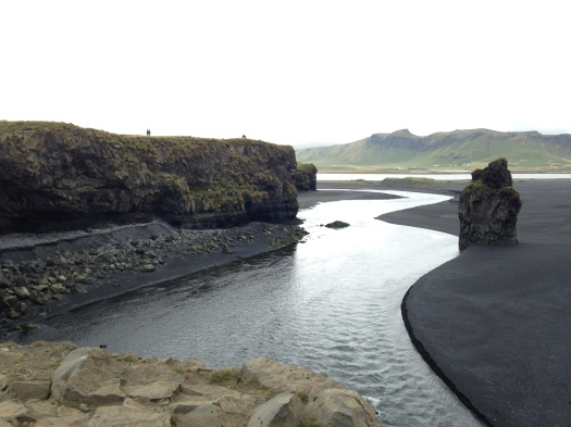 """A black sand beach replete with puffins and the distant """"troll rocks"""" (directly below) – which, legend has it, are the petrified, sunbaked corpses of a trio of trolls and the boat that they were trying to drag ashore."""
