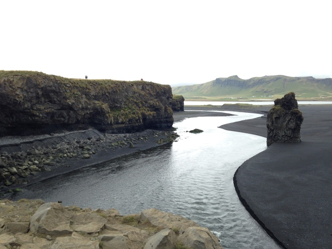 "A black sand beach replete with puffins and the distant ""troll rocks"" (directly below) – which, legend has it, are the petrified, sunbaked corpses of a trio of trolls and the boat that they were trying to drag ashore."