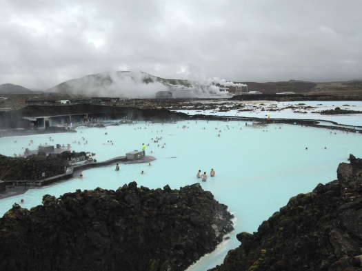 """Here are some shots of the Blue Lagoon, a geothermal spa located in the middle of a giant lava field, a place sometimes also called (by me, at least) """"the most relaxing place in the universe."""" Surrounded by saunas, steam baths, cool mist showers, caves, private massage coves, and floating bars, the water in the main bathing area averages about 100 degrees Fahrenheit and is super-rich in minerals such as silica and sulfur which work wonders on your skin and – wait for it – help cure skin diseases. Tubs of silica mud are planted about the property, there for you to rub on your face and neck and shoulders as you relax with a cocktail or a smoothie in the giant hot tub. As mentioned above, the camera couldn't quite capture the unique milky blueness of the water – not to mention the soothing drift of the steamy vapors constantly pouring up out of it."""