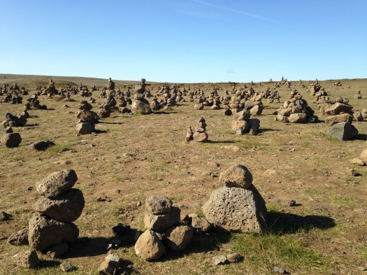 A field full of rock-towers (or cairns) spotted along the side of the road.